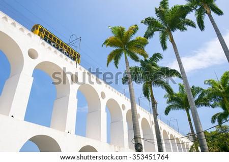 Train drives along distinctive white arches of the landmark Lapa Arches in Rio de Janeiro, Brazil - stock photo