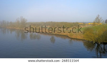 Train driving along a foggy canal in spring - stock photo
