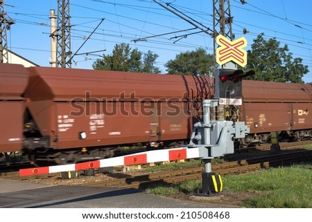 train goes over the railway crossing with gates - stock photo