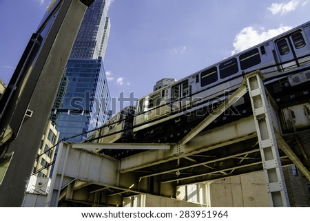 Train going through Chicago with Blue Sky and Architecture