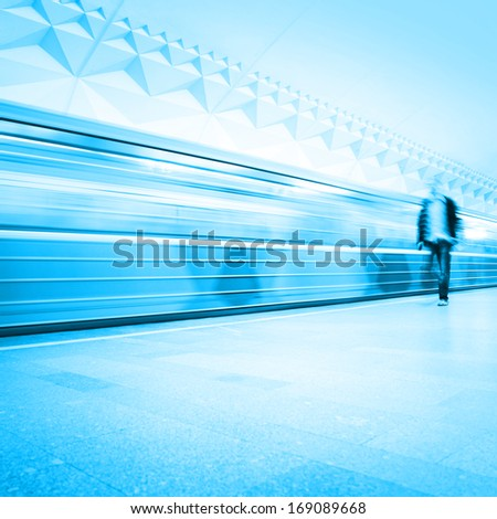 Train in motion blur and blurred commuter on background at subway station. - stock photo
