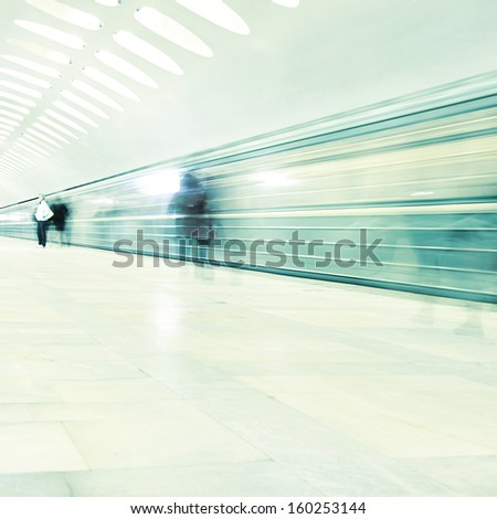 Train in motion blur and blurred people in subway station. - stock photo