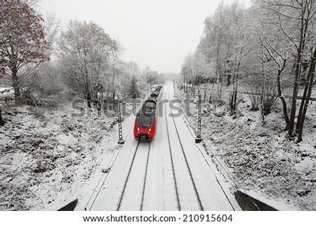 Train in snow covered winter landscape - stock photo