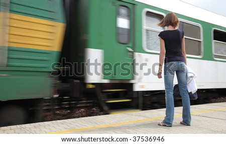 Train is coming - young woman waiting for her connection in a small town train station - stock photo