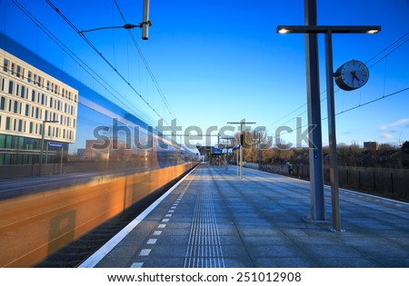 Train leaving the platform of a train station. Long exposure. - stock photo