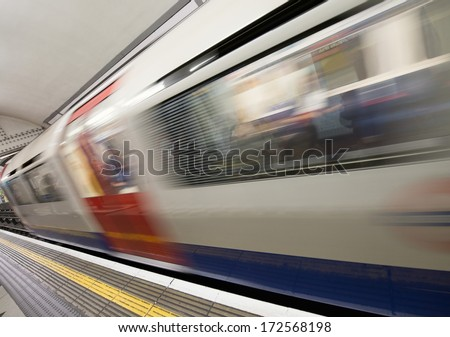 Train moving in speed at Canary Wharf platform - stock photo