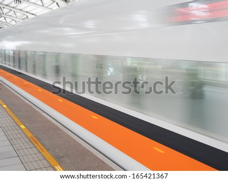 Train moving in station with motion blur
