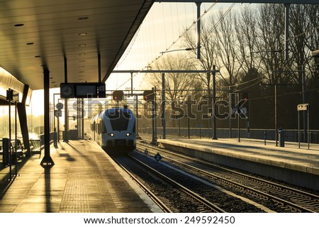 Train nearing a railway station on a winter morning. - stock photo