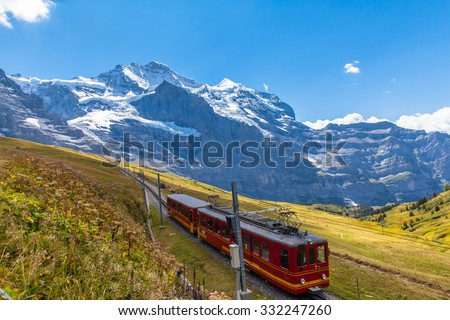 Train of Jungfraubahn running towards Jungfraujoch under the famous peak Jungfrau near the station Eigergletscher on bernese Oberland, Switzerland. - stock photo