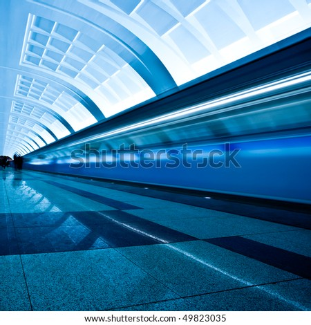 Train on underground platform in blue