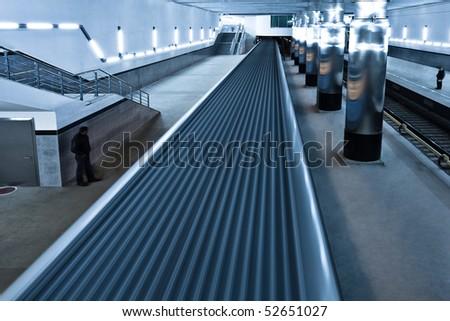 Train on underground platform in blue - stock photo