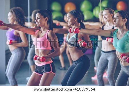 Train or remain the same. Young beautiful women in sportswear with perfect bodies exercising with dumbbells at gym - stock photo