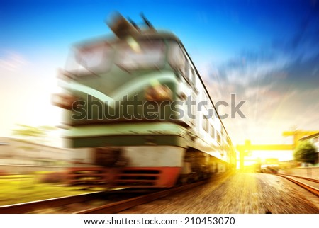 Train passing by in orange sunset - stock photo