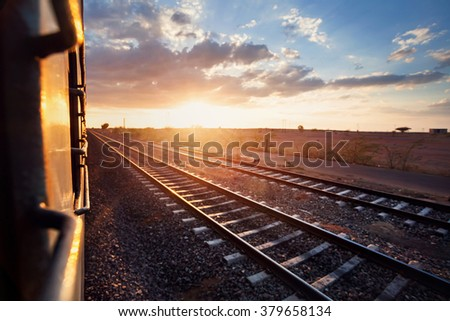 Train passing desert area at sunset sky beckgroung in Rajasthan, India - stock photo