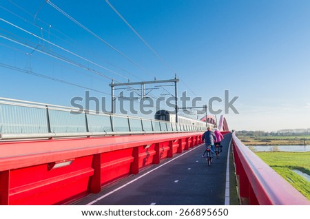 train passing the new red railroad bridge over the IJssel river in the Netherlands - stock photo