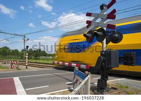 Train riding over a railway crossing in spring - stock photo