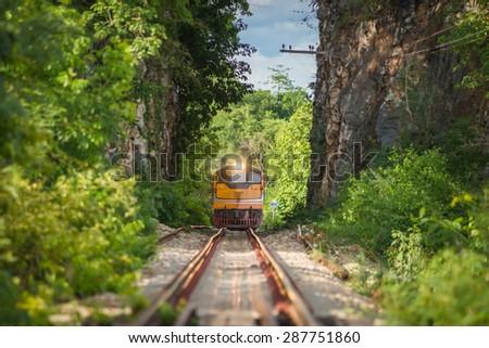 Train runs through a narrow gorge in the valley. - stock photo