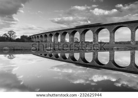 Train speeding across Arthington Viaduct, Leeds UK - stock photo