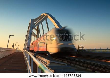 Train speeding over bridge. - stock photo