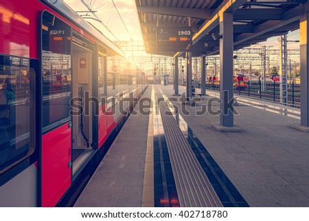 Train stands by the platform at sunset time. - stock photo
