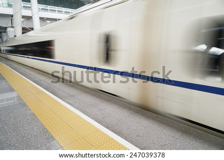 Train station and train in motion blur - stock photo