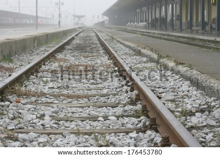 Train station with people waiting for trains on a foggy morning, pictured from rails - stock photo