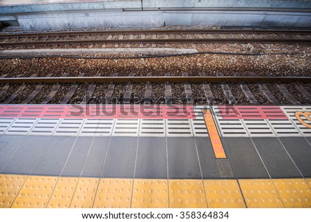 Train track railroad and waiting path, horizontal view - stock photo