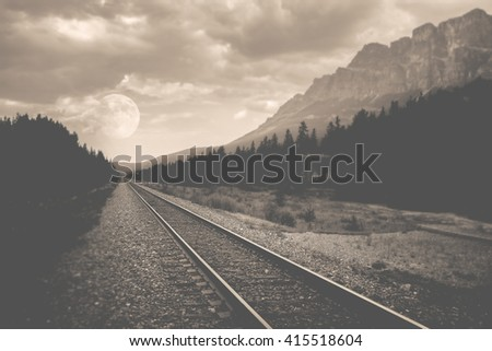 train tracks in a remote area with mountains and a full moon in a background in black and white, nature scenery with a full moon and mountain top with train tracks for traveling concept - stock photo