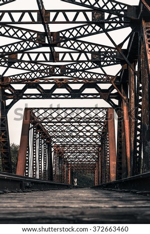 Train Tracks Reach Across a Heavy Metal Bridge. Intricate Design of Rusty Steel Beams. Low Angle with Soft Focus in Foreground Emphasizes Distant Vanishing Point.
