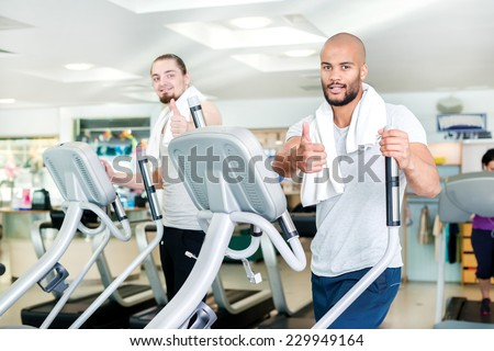 Train two friends. Workout in the gym in the cardio room. Two athletes engaged in the simulator and the gym showing thumbs up. - stock photo