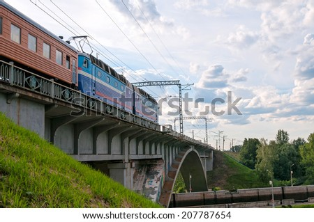 Train with multicolored locomotive and orange wagons moves on bridge against skyline background. Moscow, Russia.