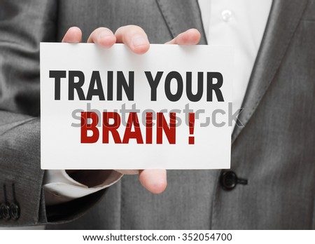 Train Your Brain ! Businessman holding a card with a message text written on it - stock photo