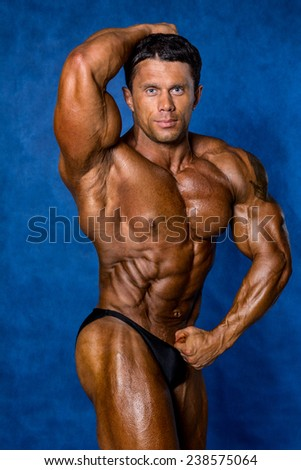 Trained bodybuilder with beautiful muscles shows her body on a blue background. - stock photo