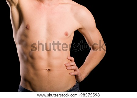 Trained young man naked torso on a black background. - stock photo