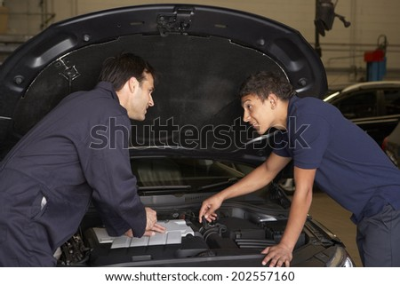 Trainee mechanic at work - stock photo
