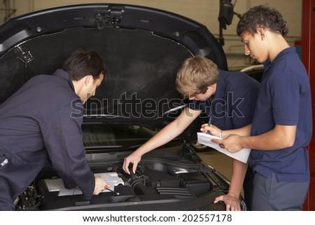 Trainee mechanics at work - stock photo