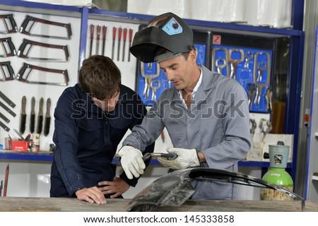 Trainee with instructor using welding machine - stock photo