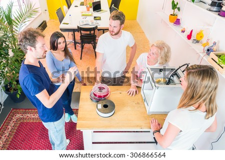 trainees and designers meeting around a 3D printer, discussing novel technologies and new product ideas and developments using 3D printing technology - stock photo