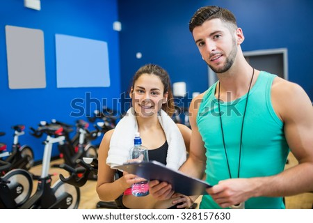 Trainer and athlete reading workout plan at the gym - stock photo