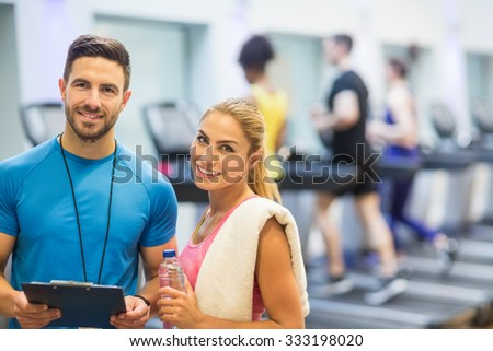Trainer and client discussing her progress at the gym - stock photo
