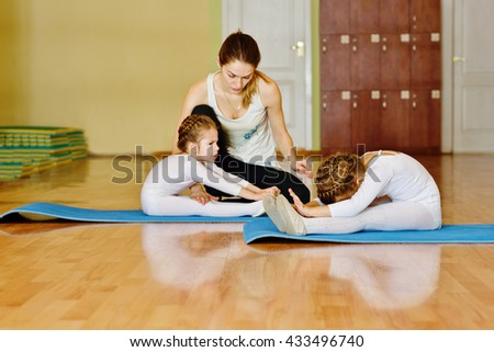 trainer and two little girls in gymnastic class