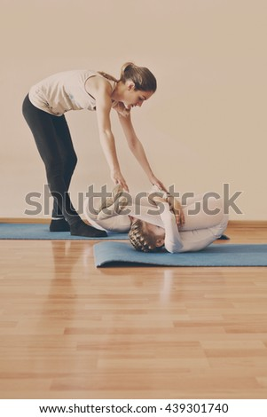 trainer and two little girls in gymnastic class - stock photo