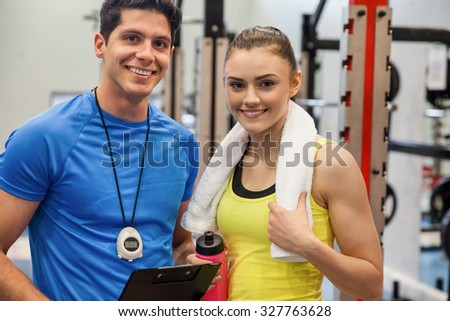Trainer and woman discussing workout plan at the gym - stock photo