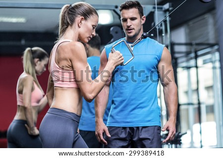 Trainer assisting a muscular woman doing pulling exercises - stock photo