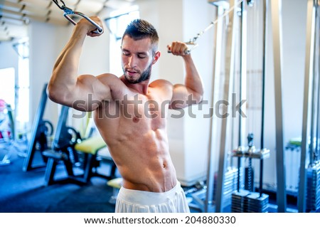 trainer, bodybuilder working out the biceps and the abs in gym on a daily workout routine - stock photo