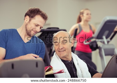 Trainer chatting to an elderly man in the gym showing him his records on a clipboard to motivate him to improve in a healthy lifestyle concept