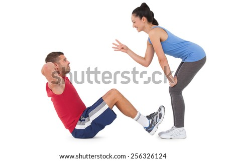 Trainer counting man doing sit ups on white background - stock photo