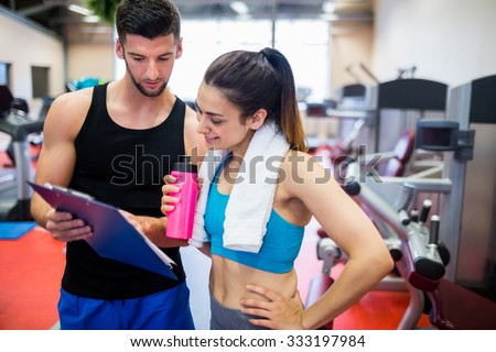 Trainer explaining workout regime to woman at the gym - stock photo