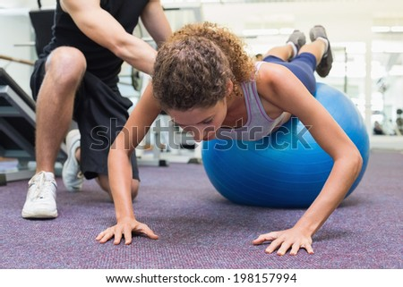 Trainer helping client workout on exercise ball at the gym - stock photo