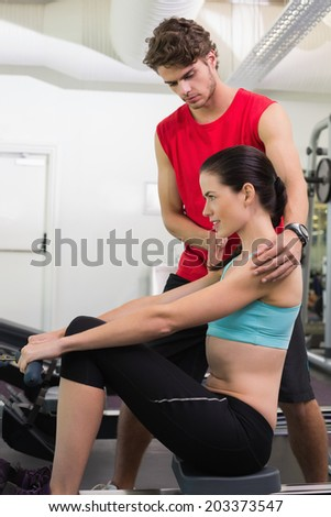 Trainer helping his pretty client on the rowing machine at the gym